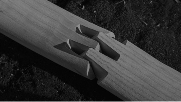 Black-and-white image of a dovetail joint, slightly separated, between two pieces of wood.