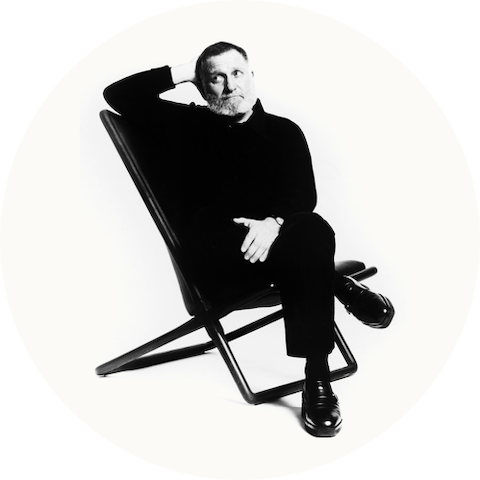Product designer Ward Bennett seated on a Sled Chair.