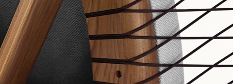 Partial view of a Crosshatch Chair, focusing on the parachute cords that support the wood frame.