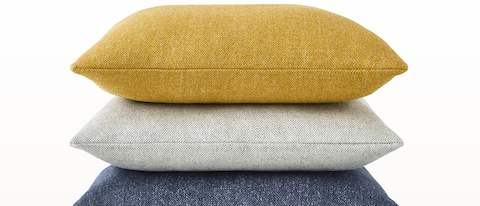 A stack of three square Geiger Textiles Pillows in yellow, light gray, and blue fabric.