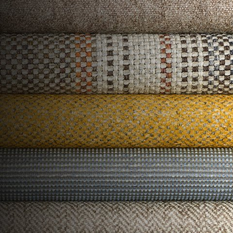 Close-up of a stack of five Geiger textiles in various colors and patterns.