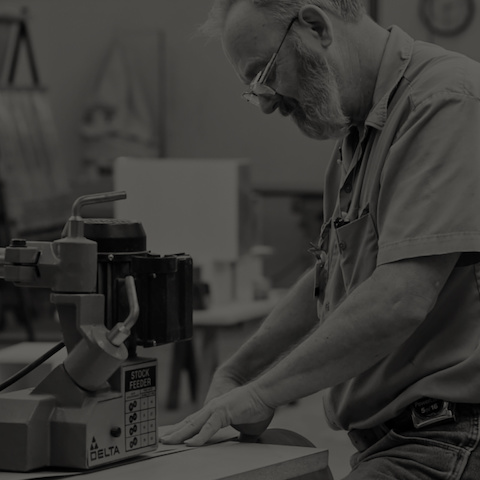 Black-and-white image of a Geiger craftsman operating a woodworking machine.