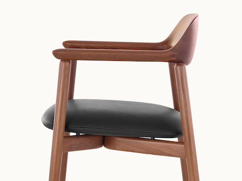 Side view of a Crosshatch Side Chair with a medium wood finish and black leather seat pad, showing the meticulous craftsmanship.