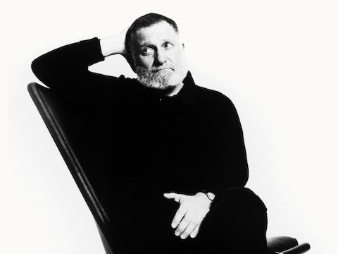 Black-and-white image of product designer Ward Bennett sitting in a Scissor Chair.