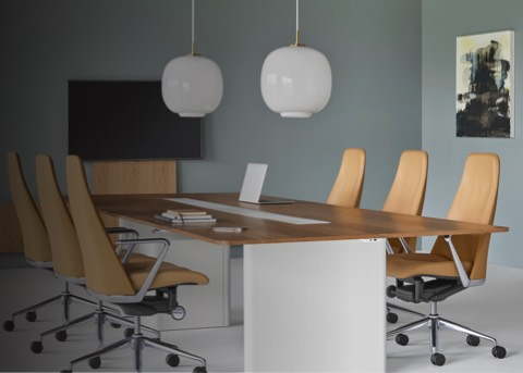 A meeting room featuring a rectangular Axon conference table with a wood top surrounded by six Taper office chairs in camel-colored leather upholstery.