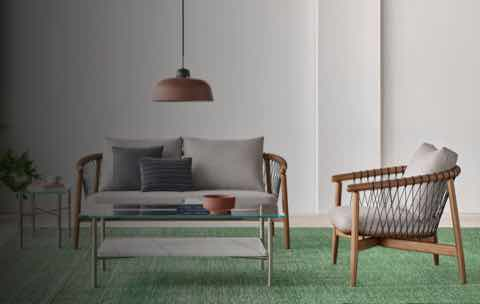 A casual lounge setting with a Layer Table anchoring a Crosshatch Settee and Crosshatch Chair.