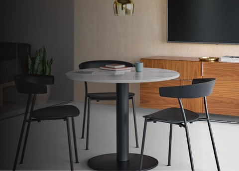 A casual work setting featuring a round Axon Table with a white Carrara Marble top. The table is surrounded by four, black Leeway Chairs. A Wood Base Sofa and a Domino Storage credenza occupy the background.