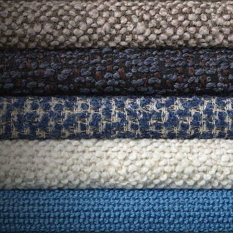 A stack of blue and neutral textiles from the Jolie Collection.