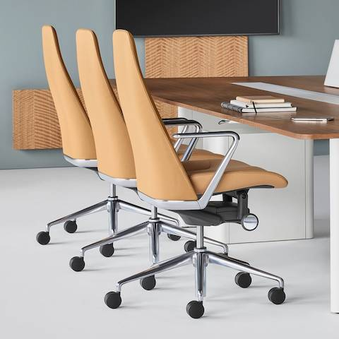 A meeting space featuring a rectangular Geiger Elsi conference table with four gray Saiba office chairs.