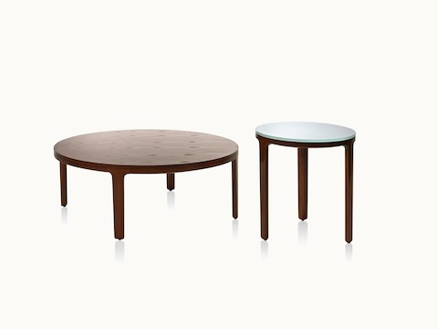 A round A Line coffee table with a veneer top and a round A Line side table with a glass top, both with solid wood legs.
