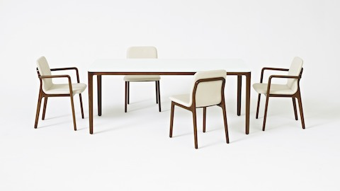A rectangular A Line meeting or dining table with a back-painted glass top, surrounded by four Deft side chairs with off-white fabric.