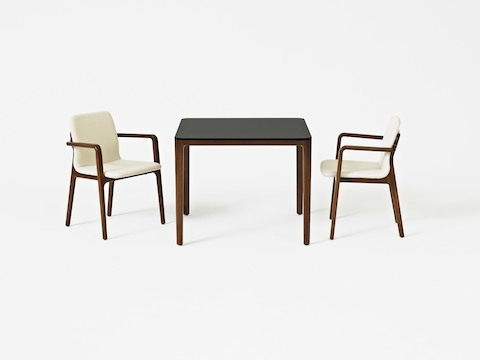 A square A Line meeting or dining table with a black top, paired with two Deft side chairs with off-white fabric.