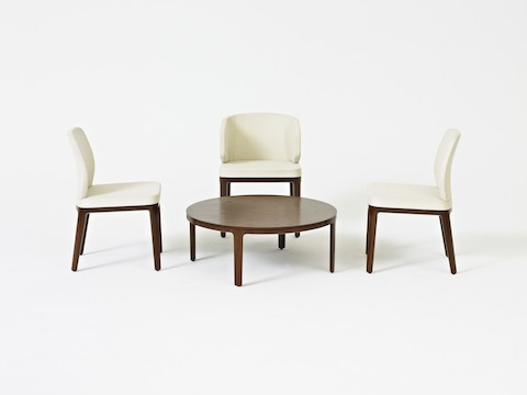 A round A Line coffee table with a veneer top, surrounded by two off-white A Line armless side chairs and one off-white A Line wingback chair.