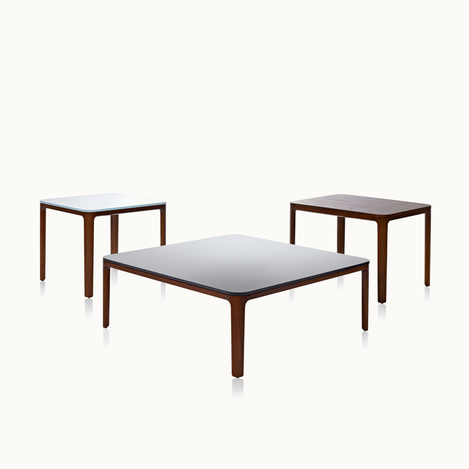Three A Line occasional tables, including two square tables with glass tops and one rectangular table with a veneer top, all with solid wood legs.