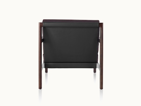 A Brabo club chair with a black leather sling, metal accents, and an exposed wood frame, viewed from behind.