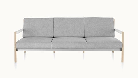 A Brabo sofa with light gray upholstery, white leather-wrapped arms, metal accents, and a light wood frame, viewed from the front.