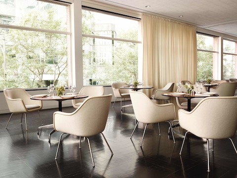 A wall of windows brings natural light into an upscale dining room featuring ivory-colored Bumper side chairs.