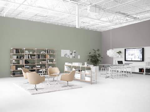 An open collaboration space featuring bookshelves, a wall-hung monitor, and a sitting area with four ivory-colored Bumper lounge chairs.