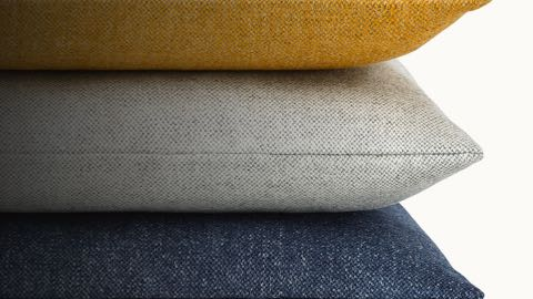 Stack of three accent pillows with gold, gray, and blue fabric.