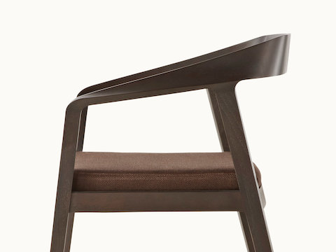 Side view of a Full Twist Guest Chair with a dark wood frame and a brown upholstered seat pad. Select to go to the Side Chairs landing page.
