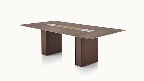 A rectangular Caucus conference table with a monolithic base and and a dark recograin rosewood veneer finish, viewed at an angle.