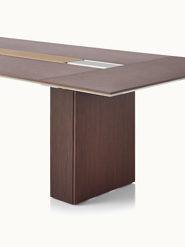 Partial angled view of a Caucus conference table with a monolithic base and a dark recograin rosewood veneer finish.