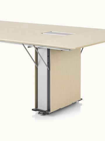 Partial angled view of a rectangular Caucus conference table with a plinth base and a light ash veneer finish.
