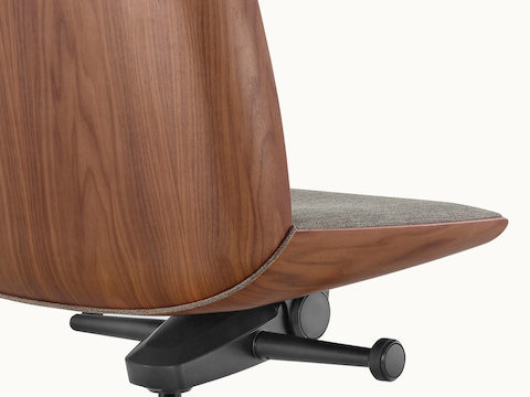 Close-up of a Clamshell office chair, viewed from behind to show the veneer shell with a medium finish.
