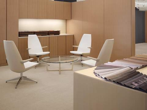 A meeting space featuring a round Loophole coffee table with a glass top surrounded by four off-white Clamshell Lounge Chairs with high backs.