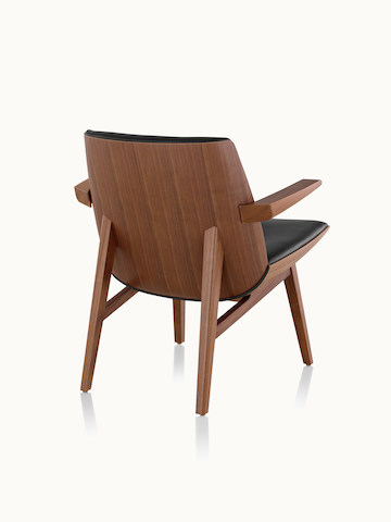 A low-back Clamshell Lounge Chair with four wood legs, viewed from behind at an angle to show the veneer shell.