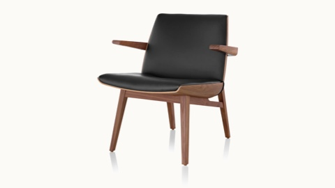 Angled view of a low-back Clamshell Lounge Chair with black leather upholstery and four wood legs.