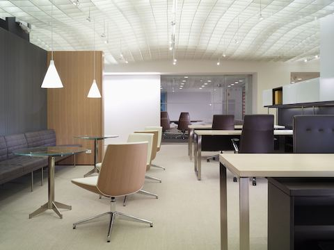 An open office featuring a variety of seating, including four Clamshell Side Chairs with ivory-colored upholstery and veneer shells in a light finish.
