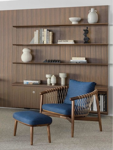 A Crosshatch Chair and Ottoman with dark blue fabric and a wood frame in a medium finish, positioned at an angle in front of bookshelves.