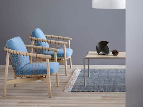 Two Crosshatch lounge chairs with light blue fabric and light wood frames, positioned next to a rectangular Full Round coffee table.