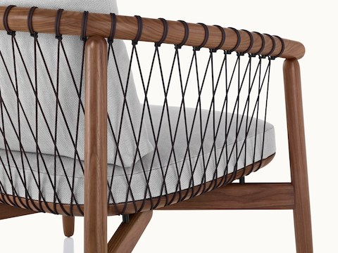 Close-up on the back and side of a Crosshatch lounge chair, showing the parachute cords that form a lattice to support the wood frame.