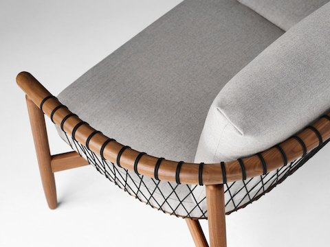 A detailed shot of a Crosshatch Settee with a walnut frame, black cords, and light neutral fabric. Viewed from the back at an angle.
