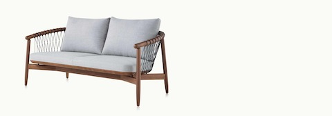 A Crosshatch Settee with a walnut frame, black cords, and a light neutral fabric, viewed at an angle.