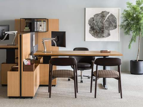 A semi-private office with a height-adjustable peninsula desk, black leather Saiba office chair, and two Crosshatch Side Chairs.
