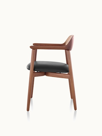 Side view of a Crosshatch Side Chair with a black leather seat pad and a wood frame in a medium finish.