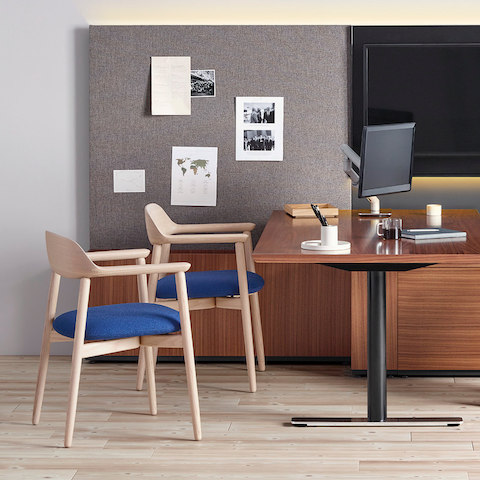 A private office featuring a peninsula desk and two Crosshatch Side Chairs with blue seat pads and wood frames.