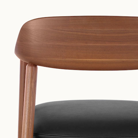 Close-up of the curved wood backrest on a Crosshatch Side Chair, viewed from behind.