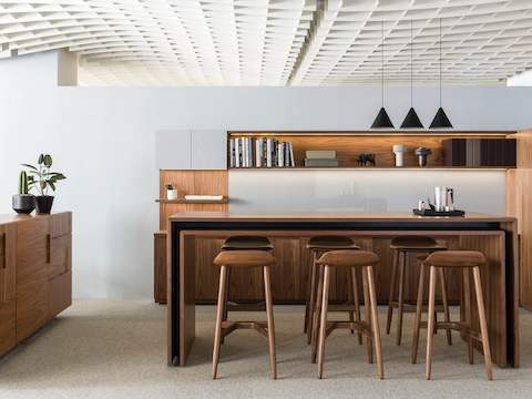 An open collaboration space featuring a rectangular Peer Table and six wood Crosshatch Stools with a medium finish.