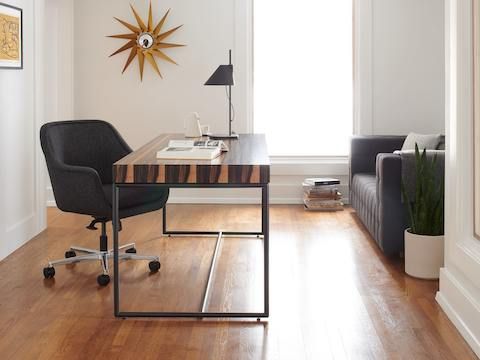 A private office featuring a Domino Desk, a Bumper Chair, and Rapport Settee.