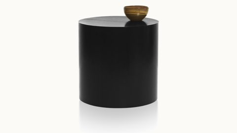 A round Drum occasional table with a dark veneer-clad base and a bowl on top.