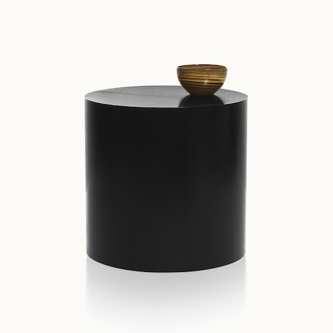 A round Drum occasional table with a dark veneer-clad base and a bowl on top. Select to go to the Drum Tables product page.