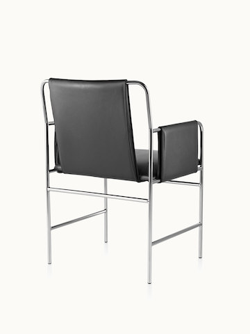 An Envelope side chair with black leather upholstery and a tubular steel frame, viewed from behind at an angle.