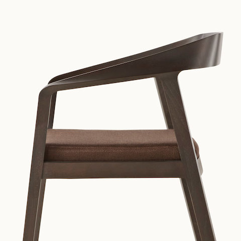Side view of a Full Twist Guest Chair, showing the ribbon-like piece of wood that forms the sculpted arms and backrest.