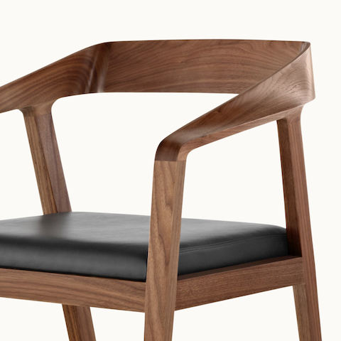 Angled view of the upper half of a Full Twist Guest Chair, showing the sculpted arms and backrest.