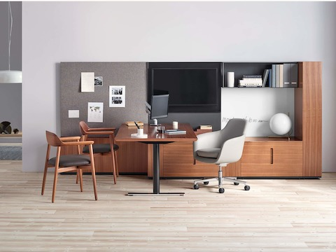 A private office featuring Geiger Rhythm Casegoods with a peninsula surface, a gray leather Saiba office chair, and two Crosshatch Side Chairs.