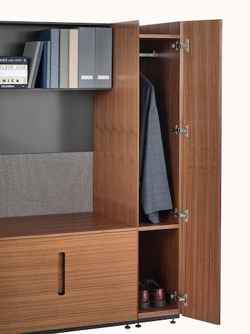 Partial view of Geiger Rhythm Casegoods, showing an open shelf holding binders and books and vertical wardrobe storage containing a jacket and shoes.